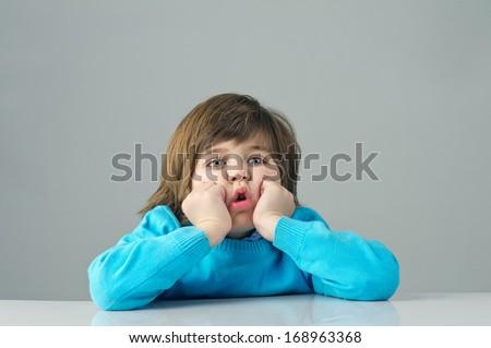 beautiful kid feeling bored isolated on grey background - stock photo