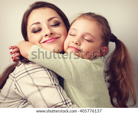 Beautiful kid girl and mother hugging with closed true enjoying. Toned closeup portrait