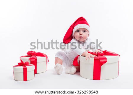 beautiful kid sitting in a New Year's cap and white body among the boxes of Christmas gifts and looking at the camera, picture with depth of field