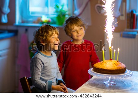 Beautiful kids, little boys celebrating birthday and blowing candles on homemade baked cake, indoor. Birthday party for children. Happy siblings about fireworks - stock photo