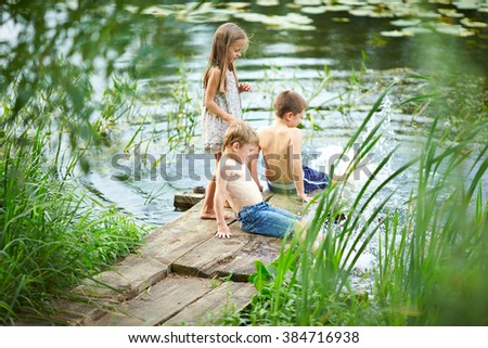 Beautiful kids on the bank of the river on a warm summer day. Sister and her brothers are playing on the bridge near the reservoir. Happy childhood.