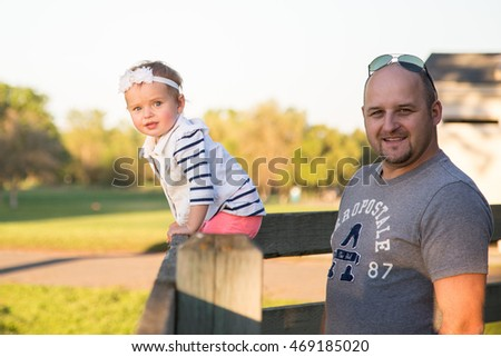 Beautiful kids with father in summer park near wooden fence