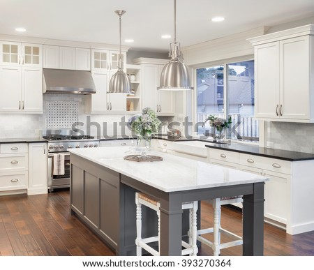 beautiful kitchen in luxury home with island, pendant lights, cabinets, and hardwood floors. tile back splash, stainless steel oven,range, and hood compliment the elegant features - stock photo