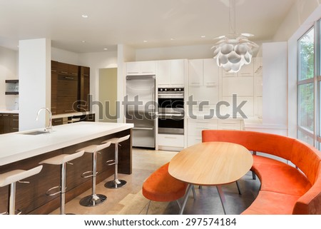 Beautiful Kitchen in New Luxury Home with Island, Sink, Cabinets, Table, Colorful Bench Seating, Refrigerator, and Oven - stock photo