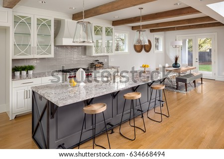Beautiful Kitchen in New Luxury Home with Large Island, Hardwood Floors, Range Hood, and Glass Fronted Cabinets, Horizontal Orientation; Lights are off