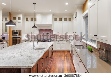 Beautiful Kitchen in New Luxury Home, with Wrap Around Cabinets, Hardwood Floors, Pendant Lights, and Large Granite Island - stock photo