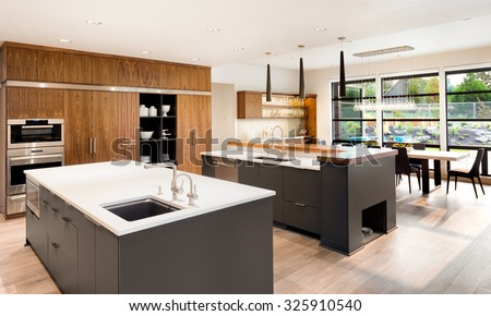 Beautiful Kitchen Interior with Two Islands,  Two Sinks, Cabinets, and Hardwood Floors in New Luxury Home - stock photo