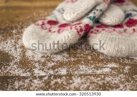 beautiful knitted mittens on a wooden background - stock photo