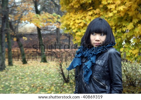 Beautiful korean girl walking in autumn park - stock photo