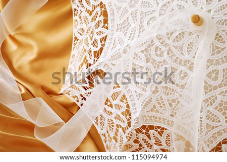Beautiful lace parasol with chiffon ribbon on gold satin background with copy space.  Macro with shallow dof. - stock photo