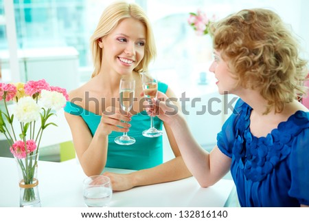 Beautiful ladies spending time together over a glass of champagne - stock photo