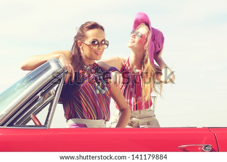 Beautiful ladies with sun glasses posing in a vintage car - stock photo