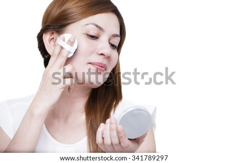 Beautiful lady applying make-up. Isolated in white background.