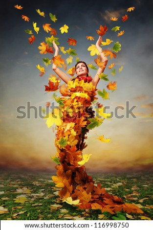 Beautiful lady Autumn in the dress from yellow maple leaves - stock photo