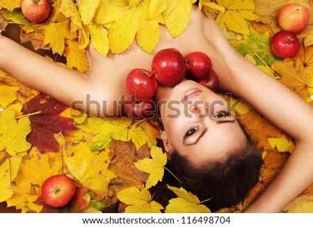 Beautiful Lady Autumn lying on the yellow leaves carpet - stock photo