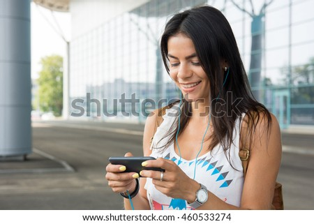 beautiful lady browsing her smart phone with headphones