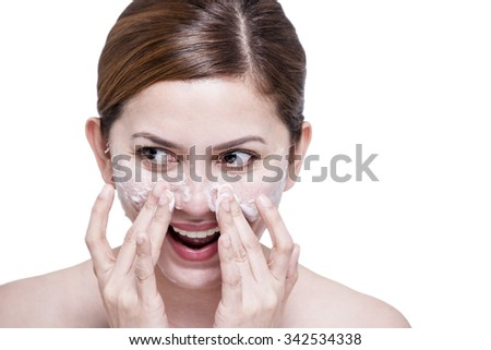Beautiful lady cleaning her face with facial soap. Isolated in white background.