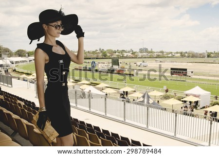 beautiful lady in a proper outfit for horse racing day on the Melbourne Cup event on hippodrome, fashion on the field - stock photo