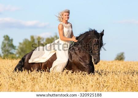 Beautiful lady in long dress riding black stallion. - stock photo