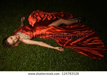 Beautiful Lady In Red Dress Lying On Green Grass - stock photo