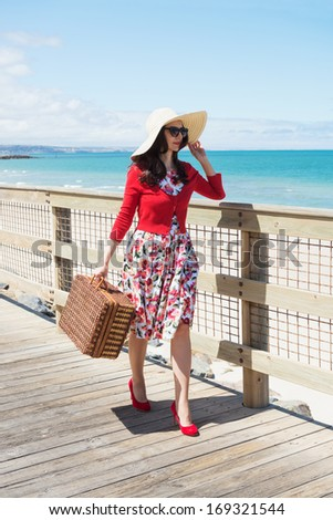 beautiful lady in red walking near the sea - stock photo