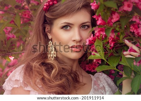 Beautiful lady in the flowers with gold earrings