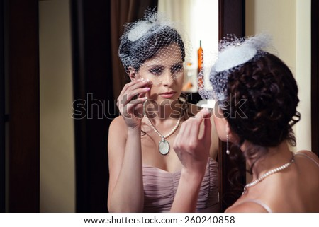 Beautiful lady in veil is looking at the mirror. - stock photo