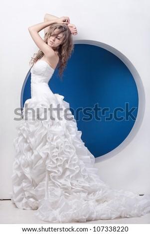 Beautiful lady in wedding dress in hi-tech interior - stock photo
