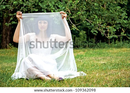 Beautiful lady in white dress ourdoors on the grass - stock photo