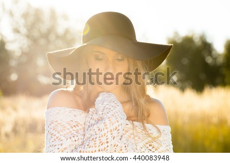 Beautiful lady model posing in an open field at sunrise - outdoors shoot - stock photo