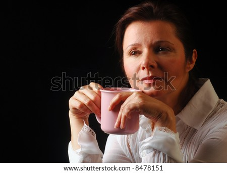 Beautiful lady musing about life while holding a cup of coffee - stock photo