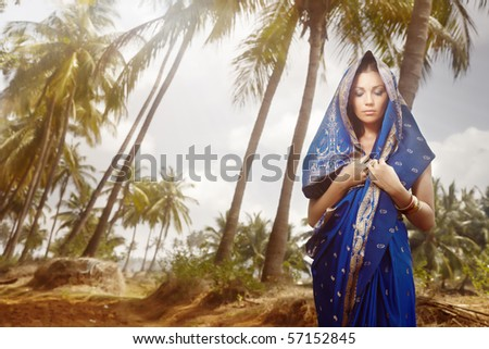 Beautiful lady outdoors in stylish sari standing in the wild jungle. Artistic colors added - stock photo