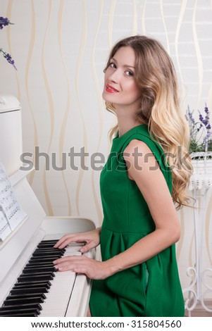 beautiful lady playing the white piano. Female sitting at the piano in green clothes on her face beautiful make-up, her hands on the keys. Women are three quarters, she looks into the camera
