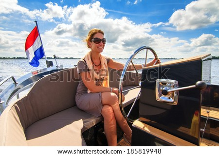 Beautiful lady sailing with a barge on a sunny summer day in the Netherlands - stock photo