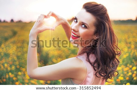 Beautiful lady showing heart symbol - stock photo