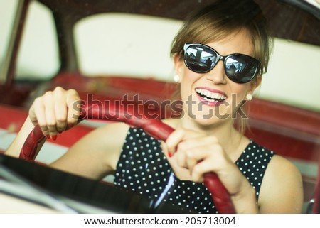 Beautiful lady sitting in a retro car - stock photo