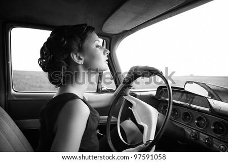 Beautiful lady sitting in a retro car - stock photo