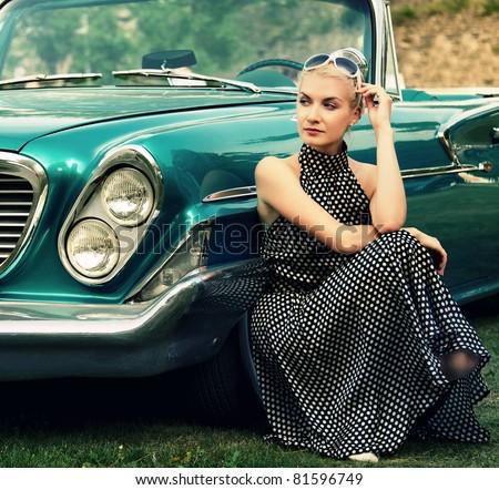 Beautiful lady sitting near retro convertible. - stock photo