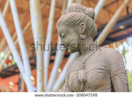 beautiful lady stone statue exteriors in nature garden - stock photo