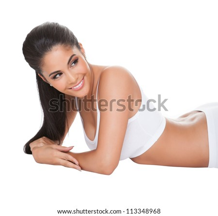 Beautiful lady with a lovely smile lying on her stomach on her bed in her underwear looking out of the frame - stock photo