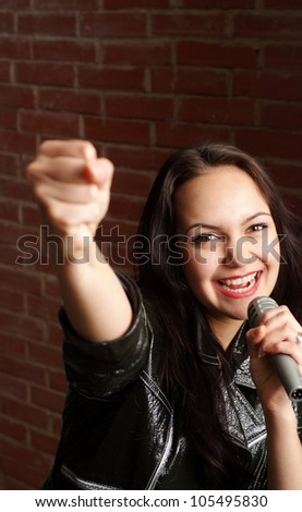 Beautiful lady with a microphone singing against a brick wall - stock photo