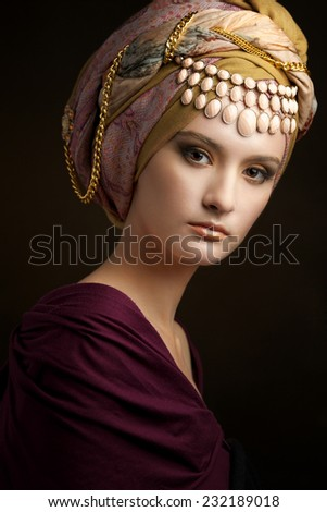Beautiful lady with colored turban against a dark background