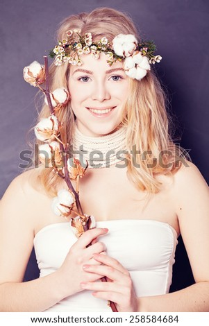 Beautiful lady with cotton flower in her hand - stock photo