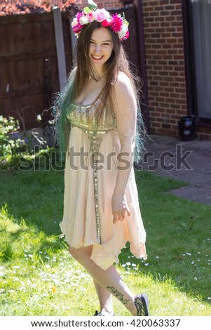 Beautiful lady with flowers in her long hair, in a garden.