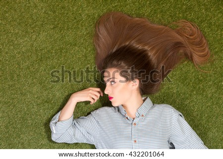 Beautiful lady with long brown hair lying on green grass and looking at her hand. Pretty woman with red lips posing for fashion magazine. - stock photo