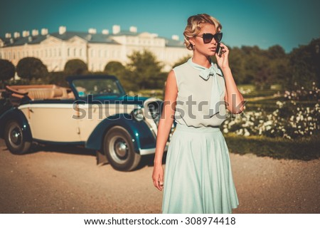 Beautiful lady with mobile phone near classic convertible - stock photo