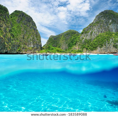 Beautiful lagoon at  Phi Phi Ley island with white sand bottom underwater and above water split view - stock photo
