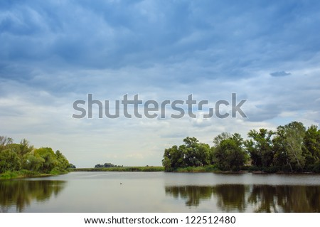 beautiful lake at the evening. Landscape - meadow, the blue sky and river - stock photo