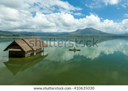 Beautiful Lake Batur landscape overlooking serene and beautiful Mount Batur during blue sky cloudy day with abandoned sub-merge house at foreground. - stock photo
