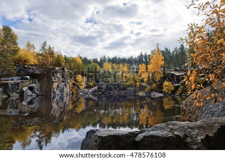 Beautiful lake in rocky quarry with fall colored trees
